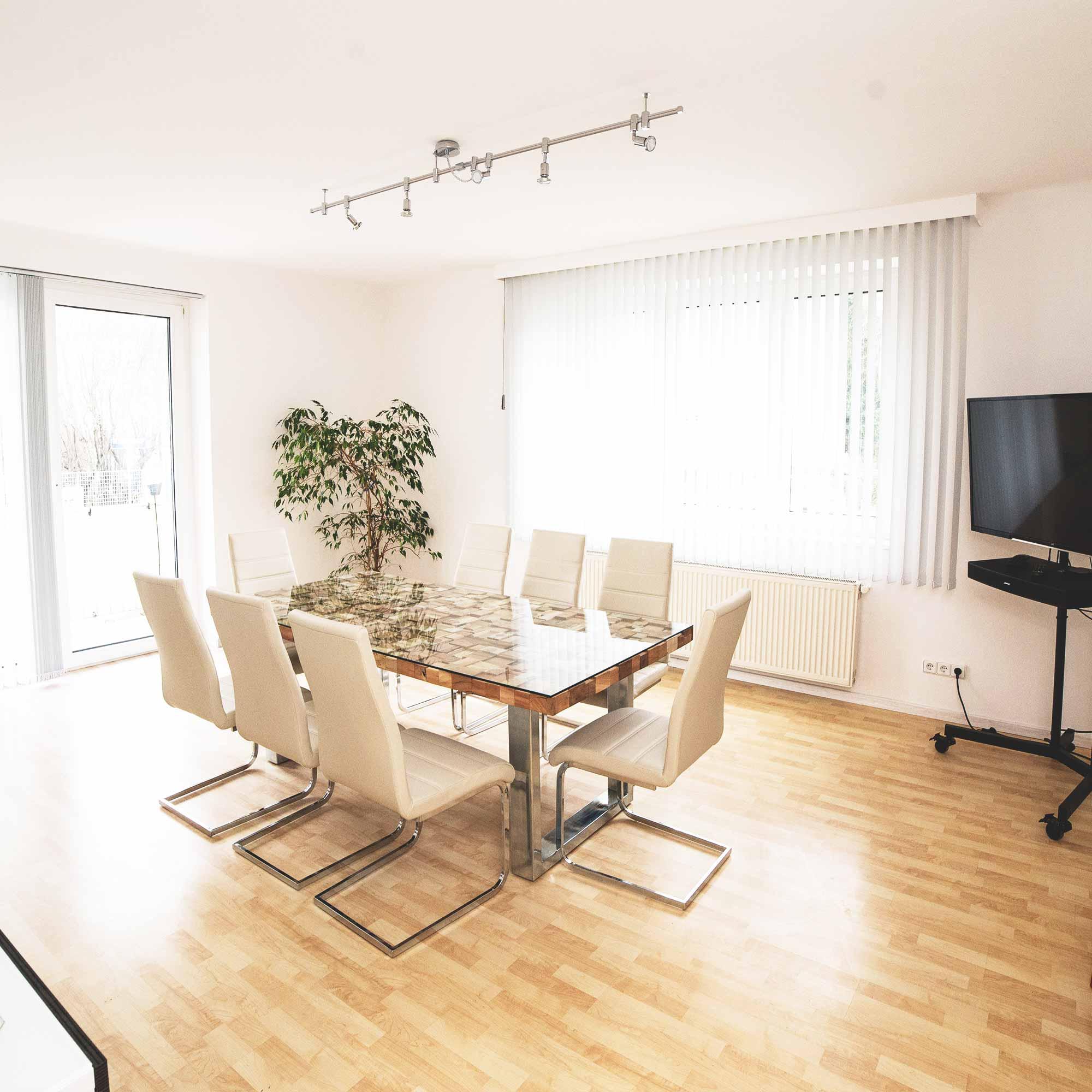 Besprechungsraum mit Tisch, Sesseln und Fernseher