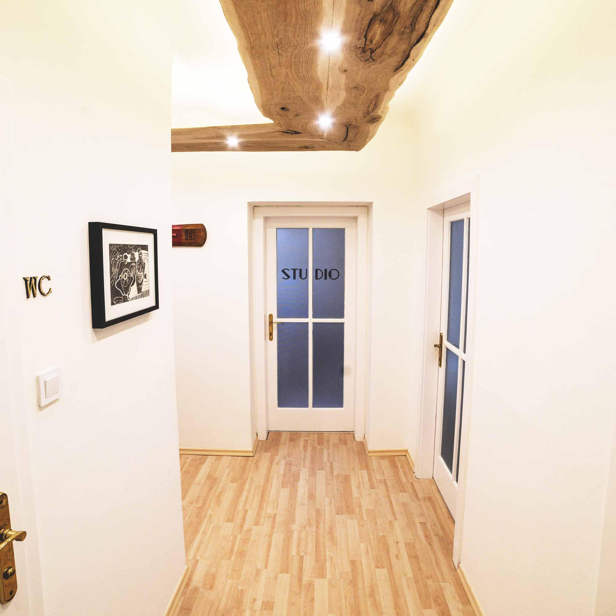 Eingangsbereich des Büros mit Holzboden und Deckenlampe aus Holz